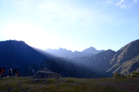 The sun rising over the mountains around machu picchu
